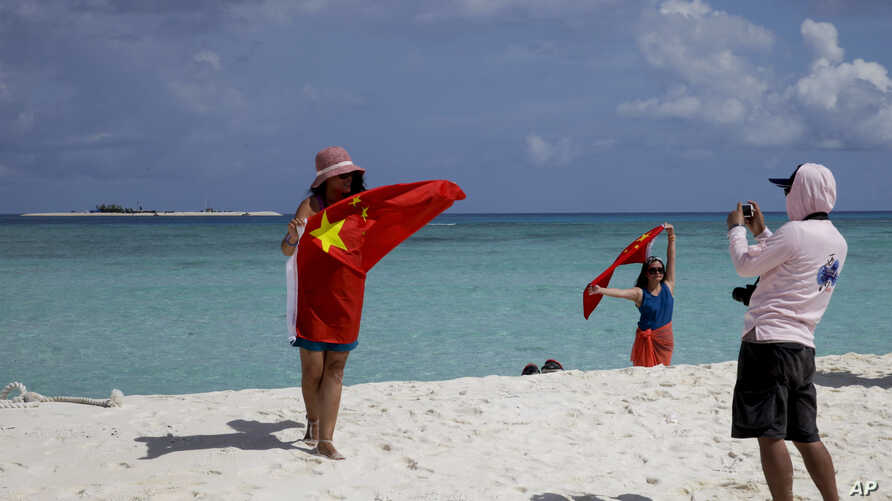 FILE - Chinese tourists take souvenir photos with the Chinese national flag as they visit Quanfu Island, one of Paracel Islands of Sansha prefecture of southern China's Hainan province in the South China Sea, Sept. 14, 2014.