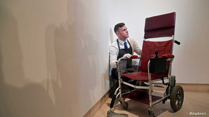 Fine-art handler Tom Richardson poses with a motorized wheelchair belonging to British theoretical physicist Stephen Hawking ahead of an auction of items from Hawkings' personal estate at Christie's in London, Oct. 30, 2018.