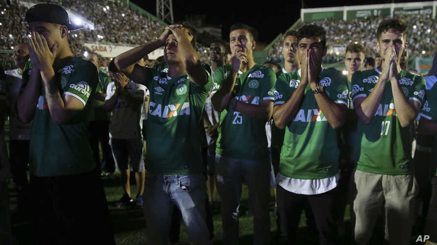 Chapecoense soccer players who did not travel with their team on a flight to Colombia, mourn during a tribute with fans to their late teammates in Chapeco, Brazil, Nov. 30, 2016.
