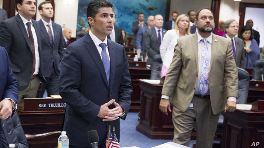Florida House bill sponsor Rep. Jose Oliva, center, (R- Hialeah), watches the vote board at the Florida Capital in Tallahassee, Fla., March 7, 2018.