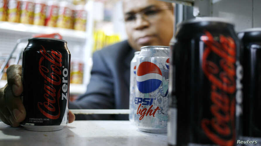 FILE - A man poses with a Coca Cola Zero can at a supermarket in Caracas.