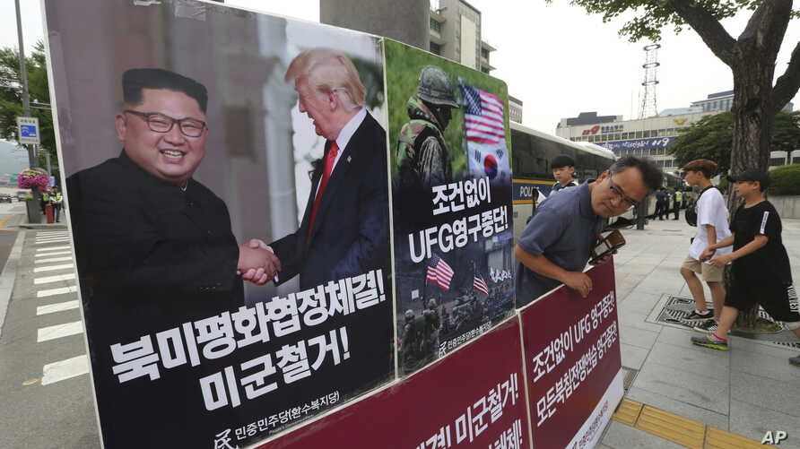 FILE - A photo showing U.S. President Donald Trump and North Korean leader Kim Jong Un is displayed as a member of People's Democratic Party stands to oppose military exercises between the United States and South Korea, near the U.S. Embassy in Seoul
