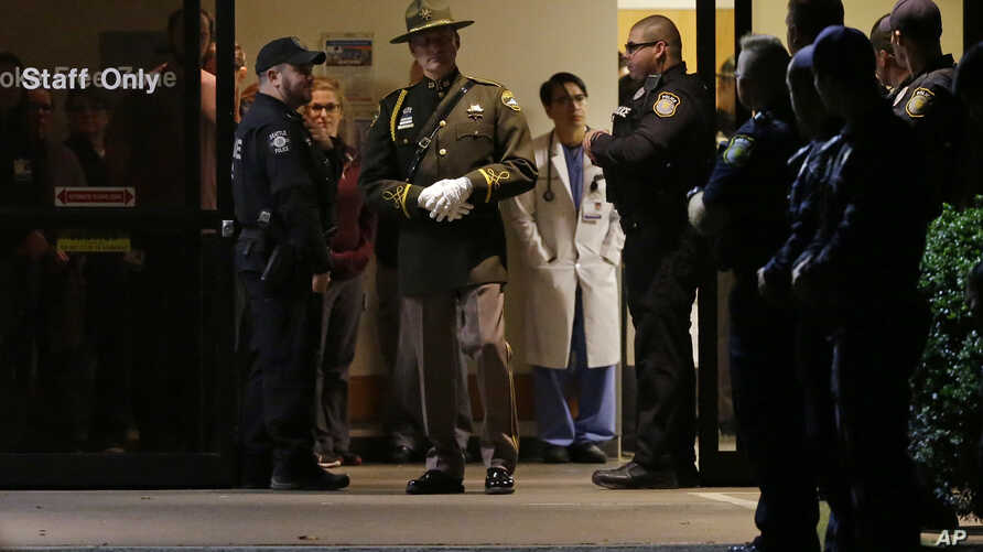 Hospital and law enforcement workers stand at an entrance to Tacoma General Hospital in Tacoma, Washington, as they wait for the body of a Tacoma Police officer who was shot and killed while answering a domestic violence call Nov. 30, 2016, to be re