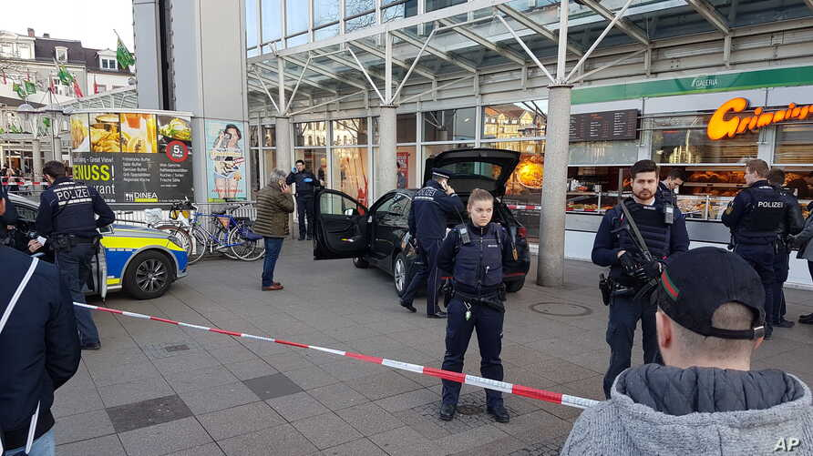 A car stands in front of a store, guarded by police in Heidelberg, Germany, Feb. 25, 2017. A man apparently drove a car into pedestrians in a central square in the city of Heidelberg, injuring three people, then fled and was shot after being tracked