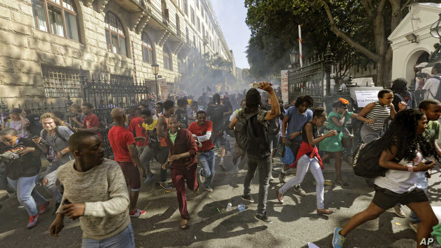 Protesting university students flee as police fire stun grenades outside Parliament in Cape Town, South Africa, Oct. 21, 2015.