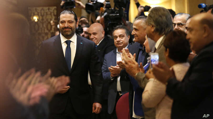 Journalists and supporters of Lebanese Prime Minister-designate Saad Hariri, left, clap as he arrives for a press conference, in Beirut, Lebanon, Nov. 13, 2018.