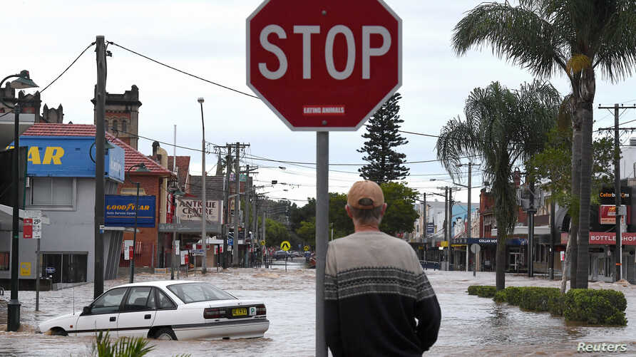 A resident watches as floodwaters enter the main street of Lismore, Australia, March 31, 2017, after heavy rains associated with Cyclone Debbie swelled rivers to record heights across the region.