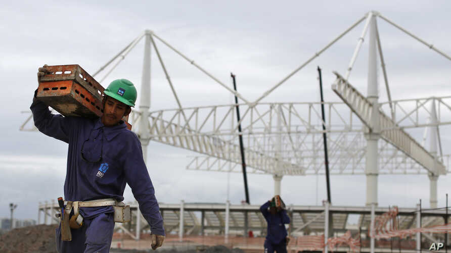 A worker carries a equipment as he walks past the aquatic stadium under construction at the Olympic Park of the 2016 Olympics in Rio de Janeiro, Brazil, March 23, 2015.
