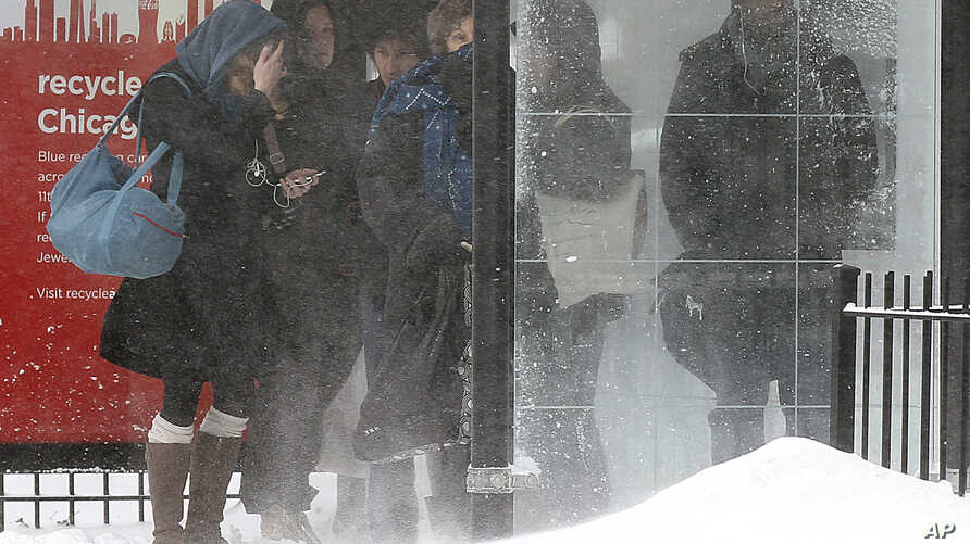 Commuters wait for their bus in blowing snow, Feb. 5, 2014, in Chicago, Illinois.