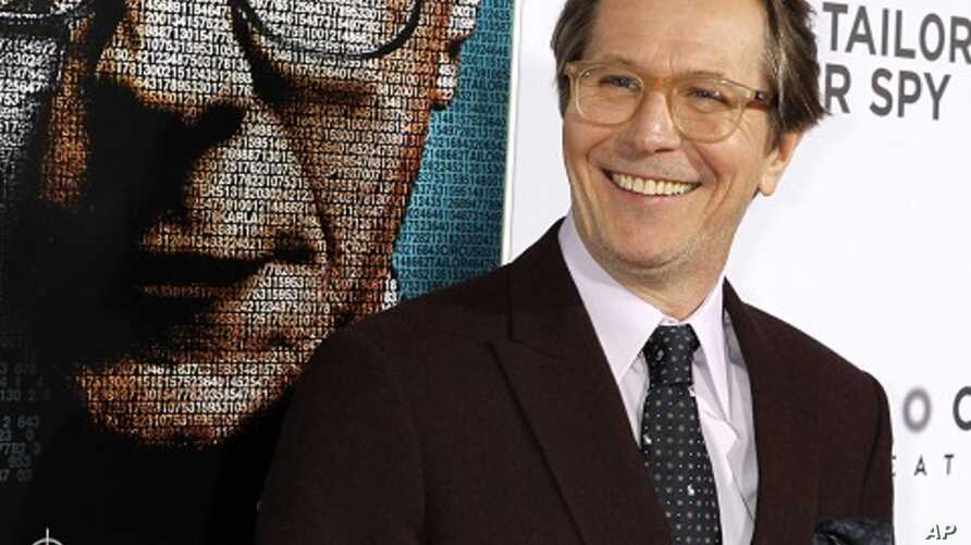 """Gary Oldman poses in front of a poster featuring his character of the film """"Tinker, Tailor, Soldier, Spy"""" at the Los Angeles premiere of the movie in Hollywood December 6, 2011."""