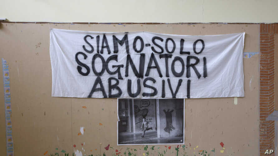 """A banner reading """"We are just unauthorized dreamers"""" is attached to the wall of the committee for """"Le Vele di Scampia,"""" (the Sails of Scampia), a public housing project which for over a decade was the center for the Camorra Mafia syndicate's drug bus"""