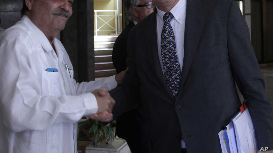 European Commission Director for the Americas and chief negotiator Christian Leffler, right, shakes hands with Cuba's Deputy Minister Abelardo Moreno before the start of their meeting in Havana, Cuba, March 4, 2015.