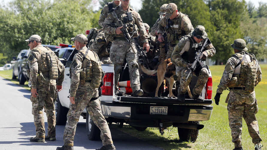 Law enforcement officers get off a truck as they return to their vehicles after searching a wooded area, June 14, 2015, in Schuyler Falls, New York.