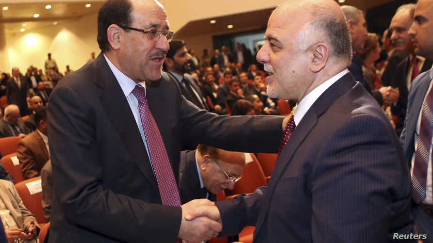 Iraq's Vice President Nouri al-Maliki (L) and new Prime Minister Haider al-Abadi shake hands during the session to approve the new government in Baghdad, September 8, 2014.Iraq's parliament approved a new government headed by Haider al-Abadi as prime