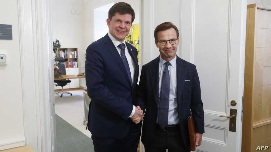 Swedish Speaker of Parliament Andreas Norlen (R) shakes hands with Swedish Moderat Party leader Ulf Kristersson at the Parliament in Stockholm, Sweden, on Oct. 2, 2018.