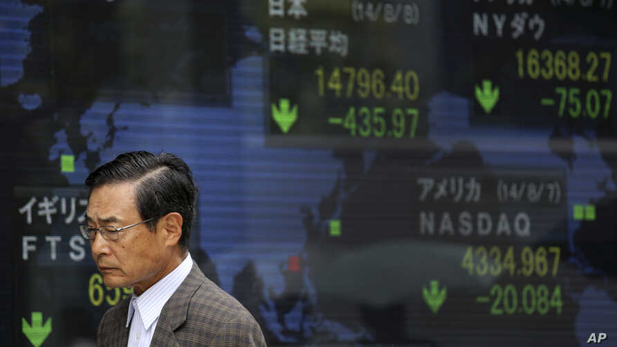 A man walks past an electronic stock board of a securities firm in Tokyo as the 225-issue Nikkei Stock Average, shown top center, dived 454.00 points, or 2.98 percent, and finished at 14,778.37, hitting a two-month low Friday, Aug. 8, 2014. Asian sto