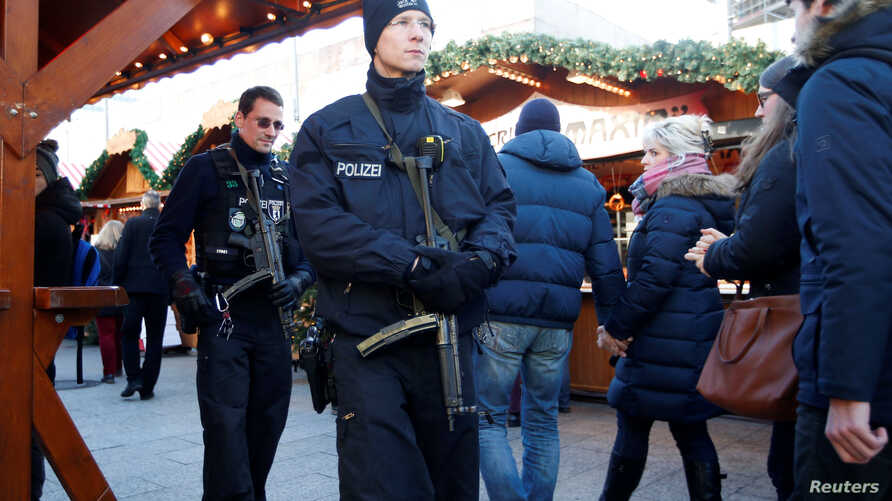 German police patrol with submachine guns at the Christmas market at Breitscheid square in Berlin, Dec. 30, 2016, following an attack by a truck which ploughed through a crowd at the market.
