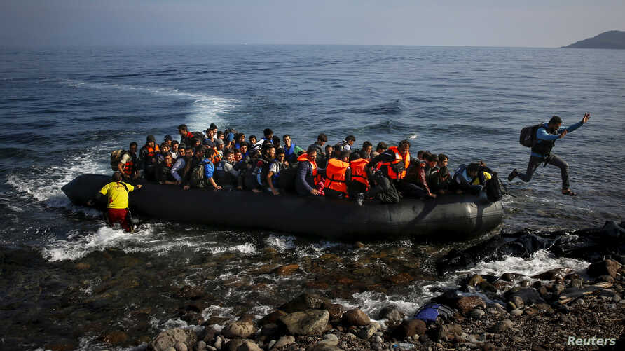 FILE- An Afghan migrant jumps off an overcrowded raft onto a beach in the Greek island of Lesbos, Greece.