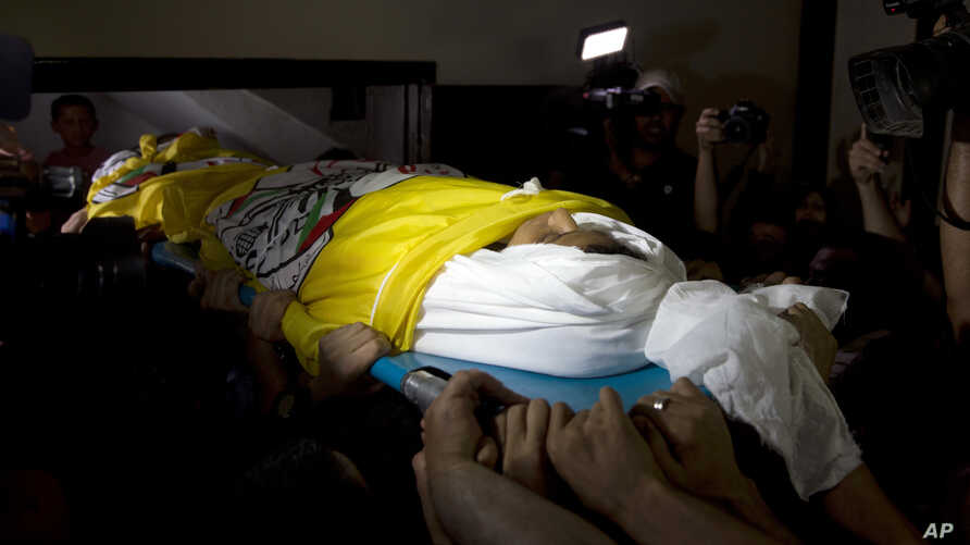 Palestinian mourners carry the body of 15-year-old Othman Hilles, out of the family home during his funeral in Gaza City, Saturday, July 14, 2018. Hilles was killed on Friday by Israeli fire at a border protest, Gaza's Health Ministry said.