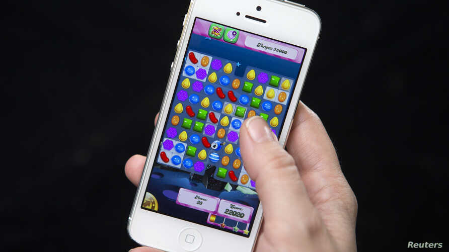 Woman poses for photo illustration with iPhone as she plays Candy Crush, New York, Feb. 18, 2014.