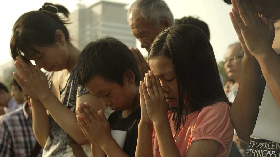 Visitors pray for the atomic bomb victims in front of the cenotaph at the Hiroshima Peace Memorial Park in Hiroshima, western Japan, Thursday, Aug. 6, 2015.