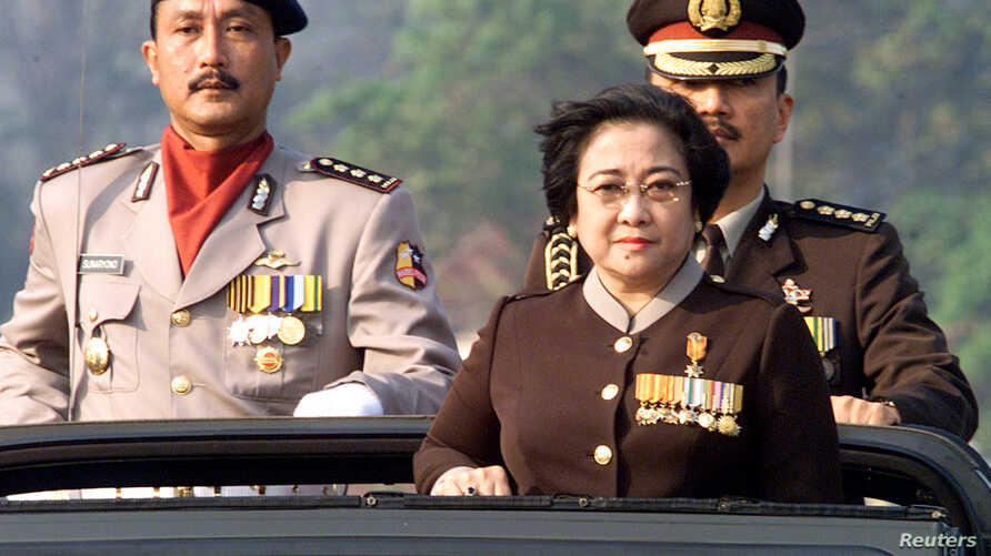 Indonesian President Megawati Sukarnoputri, flanked by her adjutantColonel Budi Gunawan (R) and ceremony commander Police CommissionerSunaryono (L) at the 56th anniversary of the country's police force inJakarta on July 1, 2002. In an address to some