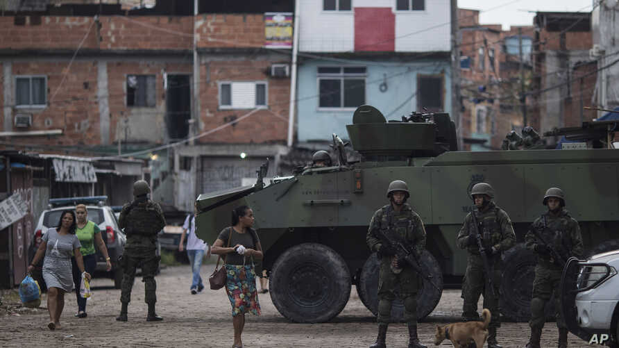 Brazilian marines stand in guard next to an armored vehicle a during surprise operation in Kelson's slum in Rio de Janeiro, Brazil, Feb. 20, 2018.