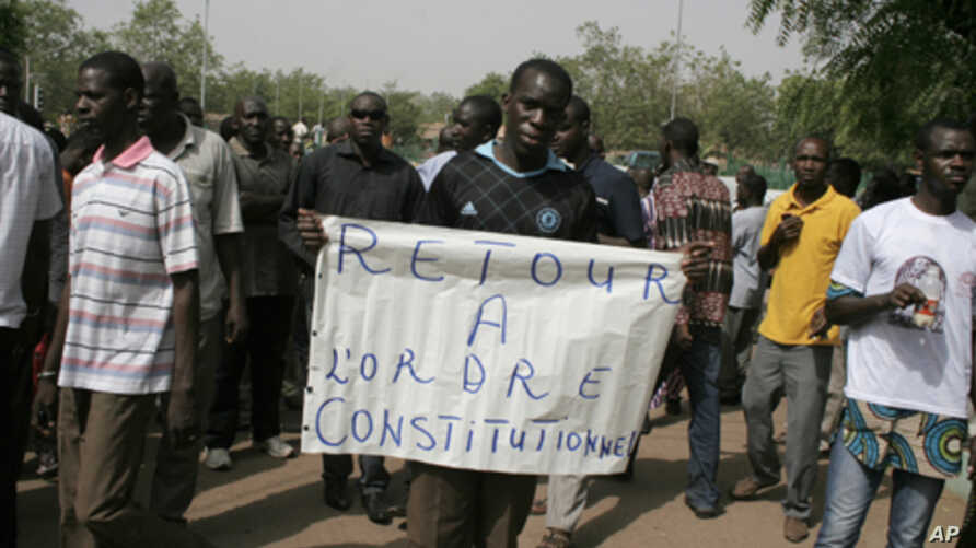 A man carries a sign reading 'Return to constitutional order,' as people gather in protest against the recent military coup, in Bamako, Mali on Monday, March 26, 2012.