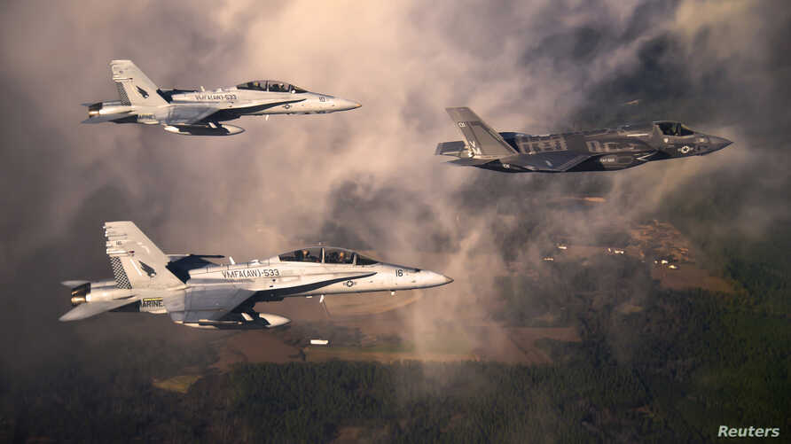 """A U.S. Marine Corps F-35 Lightening II multirole fighter jet (R) is escorted by two USMC F-18 Hornets as it flies towards Eglin Air Force Base, Florida in this U.S. Air Force handout photo dated January 11, 2012. The Pentagon is preparing to lift a """""""