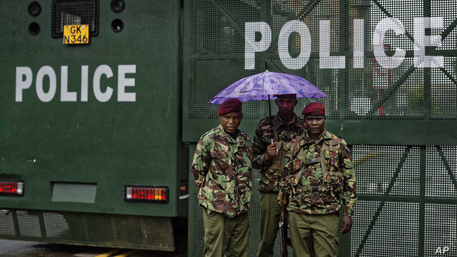 Kenyan police stand in the rain by a barrier blocking off vehicle and pedestrian access, amid tight security outside the Supreme Court in Nairobi, Kenya, Nov. 14, 2017.