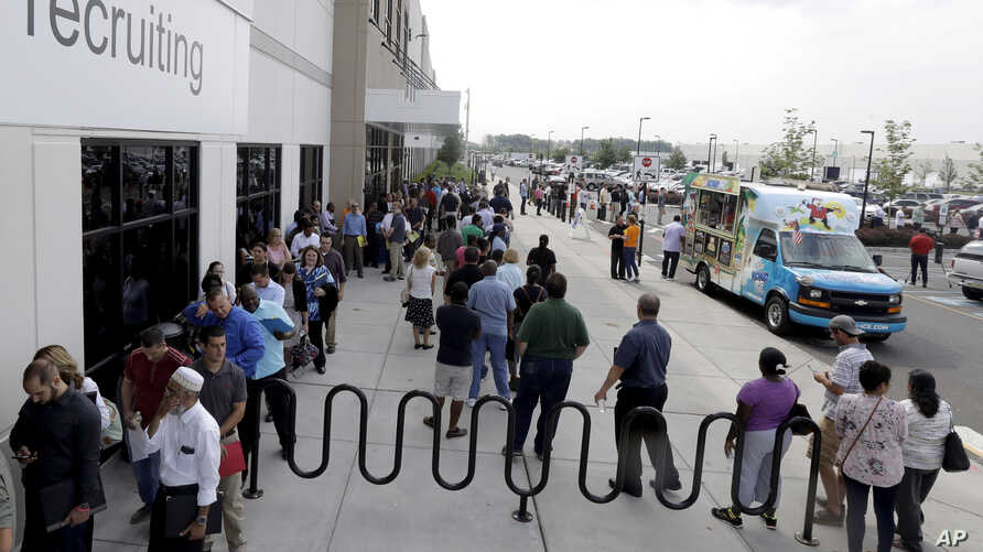 Job candidates wait in lines outside the recruitment office at the Amazon fulfillment center in Robbinsville, N.J., during a job fair, Aug. 2, 2017