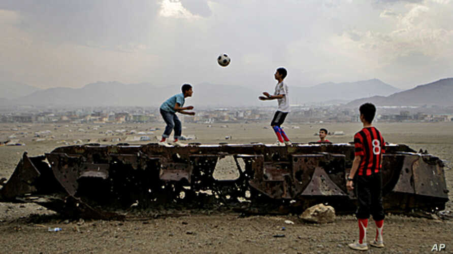 Afghan boys play with a ball on top of the remains of a Russian armored vehicle in Kabul, Afghanistan, October 6, 2011.