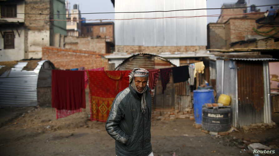 FILE - A man walks past a temporary shelter built near houses which were damaged during the earthquakes last year, in Bhaktapur, Nepal.