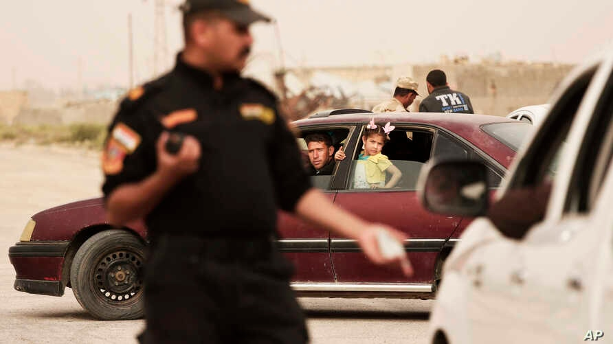 An Iraqi counter terror officer talks to people in a convoy of families fleeing Islamic State-held Hit, Iraq, at a checkpoint on the western edge of Ramadi, Iraq, March 20, 2016.