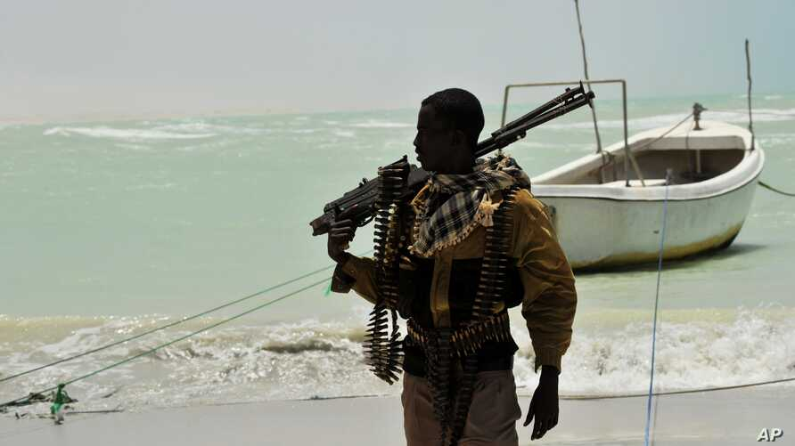 A Somali, part armed militia, part pirate, carries his high-caliber weapon on a beach in the central Somali town of Hobyo on August 20, 2010.