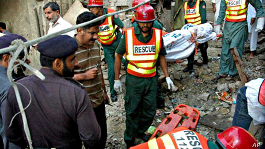 Pakistani police officers visit the site of explosion as rescue workers remove a dead body after a bomb blast in the shrine of Sufi Farid Shakar Ganj in Pak Pattan, west from Lahore, 25 Oct. 2010