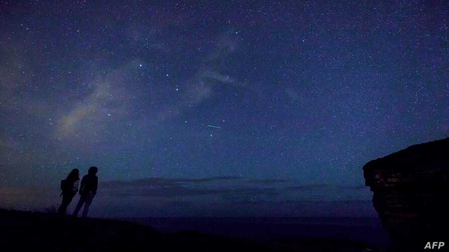 """This picture taken on August 12, 2017 shows a couple enjoying Perseid meteor along the Milky Way illuminating the dark sky near Comillas, Cantabria community, northern Spain, during the """"Perseids"""" meteor shower."""