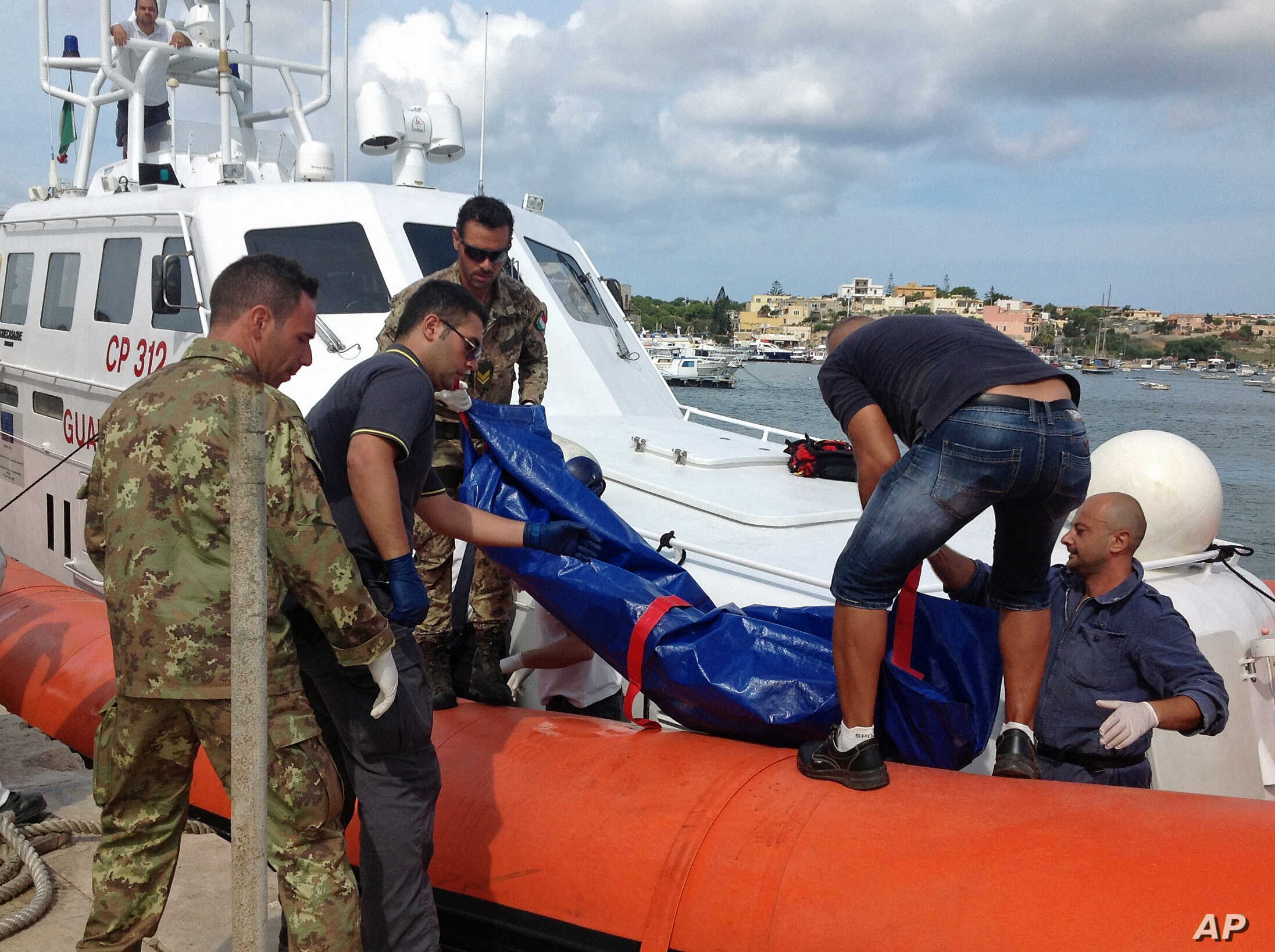 The body of a drowned migrant is being unloaded from a Coast Guard boat in the port of Lampedusa, Italy, Oct. 3, 2013.
