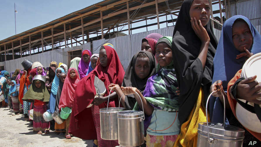 FILE - Displaced Somali girls who fled the drought in southern Somalia stand in a queue to receive food handouts at a feeding center in a camp in Mogadishu, Somalia.
