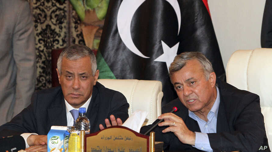 Libyan Prime Minister Ali Zidan, left, gives a press conference after being rescued from gunmen who snatched him from his hotel early Oct. 10, 2013.