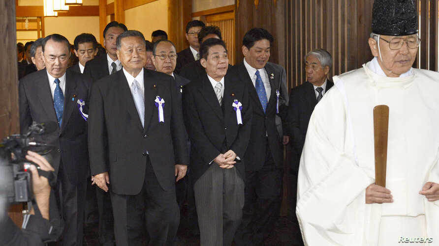 Japanese lawmakers, including cabinet ministers, are led by a Shinto priest as they visit the Yasukuni Shrine for the war dead in Tokyo, October 18, 2012.