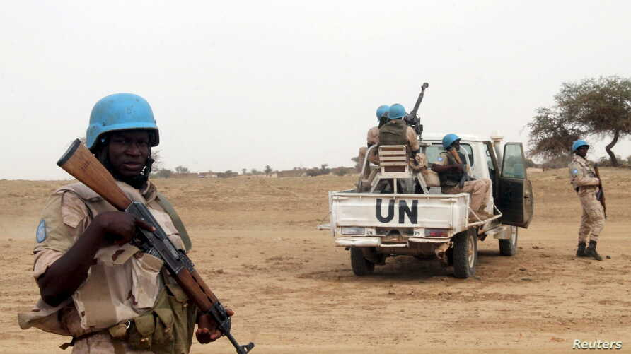 FILE - UN peacekeepers stand guard in the northern town of Kouroume, Mali.