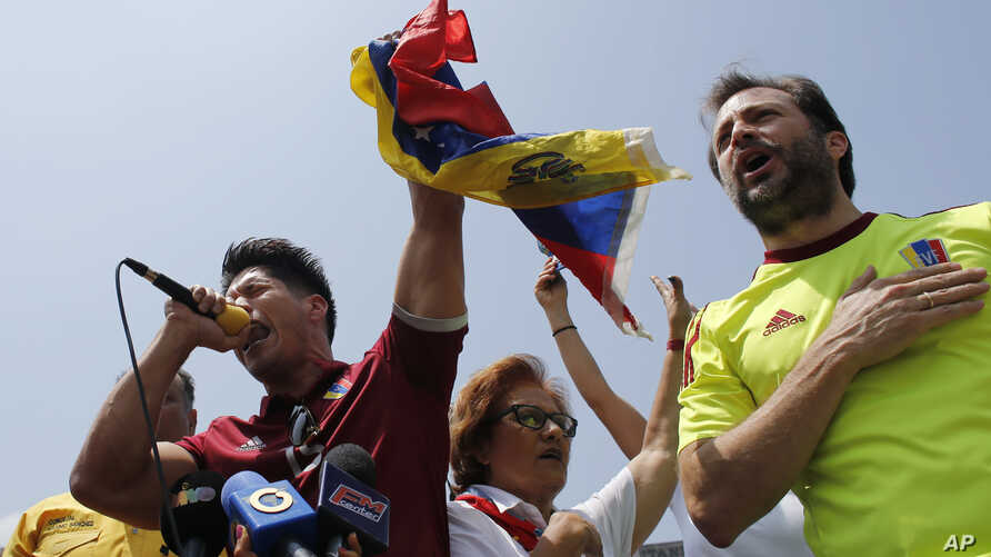 FILE - Chacao Mayor Ramon Muchacho, right, and Venezuelan singer Jesus Alberto Miranda, known as Chino, sing the national anthem during an anti-government protest in Caracas, Venezuela. Venezuela's high court ordered the removal and arrest of Muchach