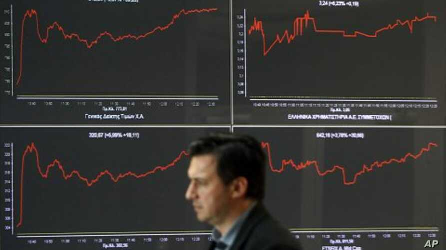A man walks past an index board at a hall of the Athens Stock Exchange in Athens October 27, 2011. Greek bank stocks jumped more than 13 percent in early morning trade on Thursday after euro zone leaders agreed a new rescue deal for Greece, despite p