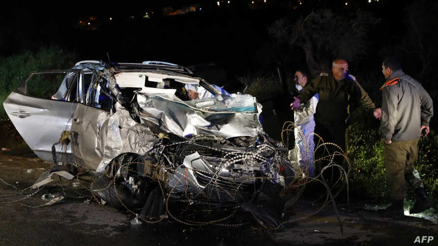 Israeli security forces and forensics inspect the destroyed vehicle that was used by a Palestinian assailant in a ramming attack targeting a group of Israeli soldiers near Mevo Dotan in the north of the occupied West Bank, March 16, 2018.