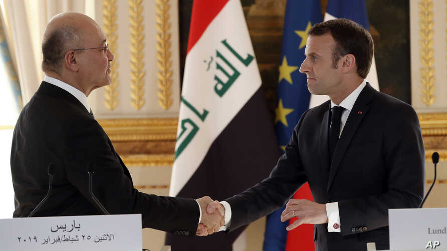 French president Emmanuel Macron, right, shakes hands with Iraqi President Barham Saleh after a press conference at the Elysee Palace in Paris, Feb. 25, 2019.