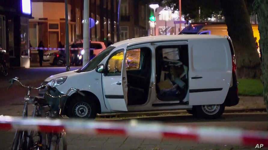 In this image taken from video, a van is examined behind a cordoned-off area in Rotterdam, Aug. 23, 2017, after a possible terror threat resulted in the cancellation of a concert by an American bnad. Police detained the driver of a van with Spanish l