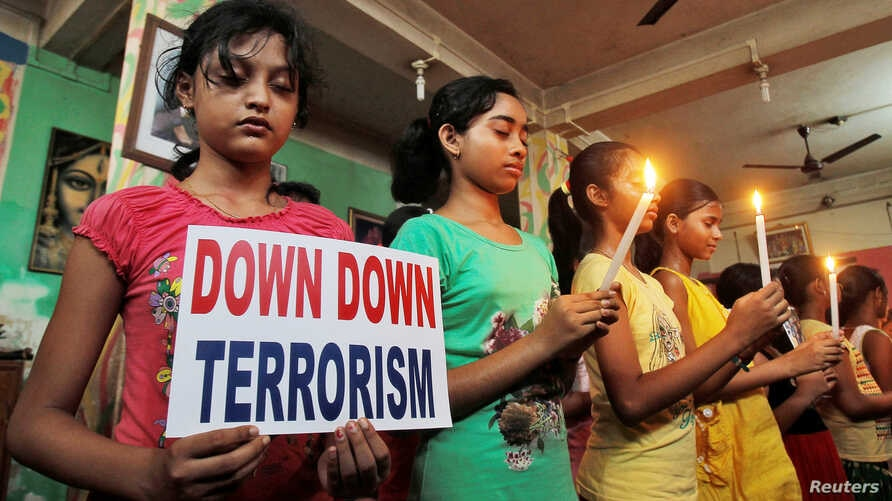 Students hold placard and candles as they pray to show solidarity with the victims of the attack on the Holey Artisan Bakery and the O'Kitchen Restaurant at Dhaka, Bangladesh, during a vigil in Agartala, India July 3, 2016.
