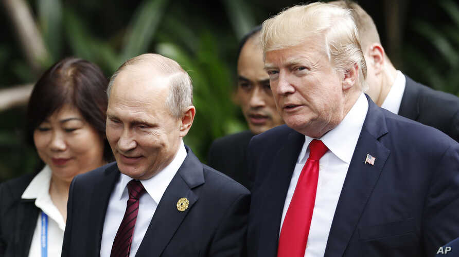 U.S. President Donald Trump, right, and Russia's President Vladimir Putin, center, talk during a group photo session at the APEC Summit in Danang, Nov. 11, 2017.