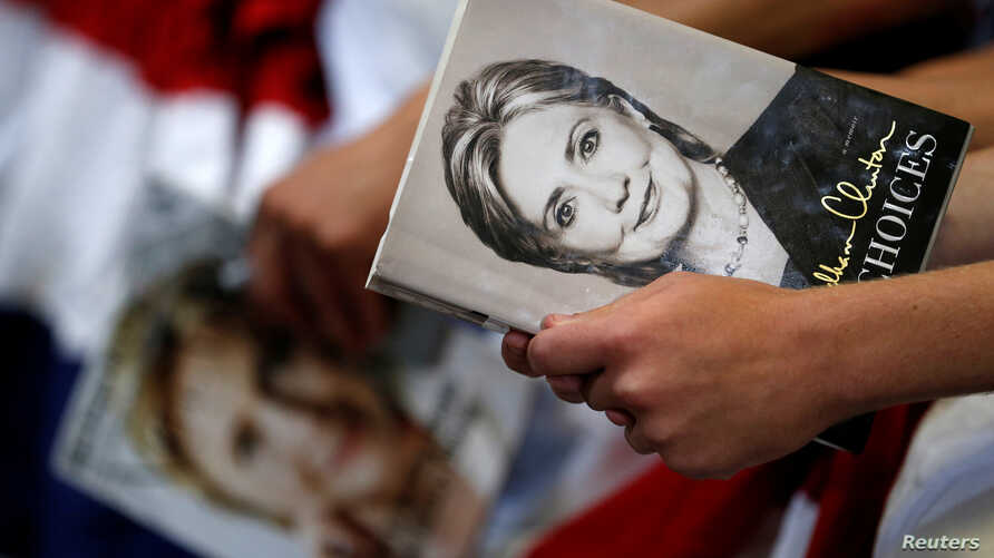 "FILE - A supporter holds the book ""Hard Choices"" by Democratic U.S. presidential candidate Hillary Clinton before she speaks at a campaign event at the North Carolina State Fairgrounds in Raleigh, North Carolina, June 22, 2016."